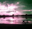 sonnendurchfluteter wolkenhimmel in pink, darunter wasser, ein fahrrad davor auf dem strand